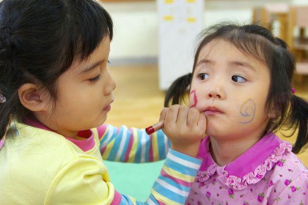 幼儿园里 两个小朋友 在脸上画画